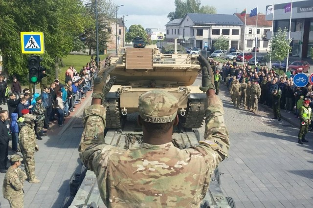 Sgt. Andre Richardson from the 51st Transportation Company, 39th Transportation Battalion (Movement Control), 16th Sustainment Brigade, 21st Theater Sustainment Command, directs the loading of an M1A2 Abrams tank in Marijampole, Lithuania, on August 13, 2015.