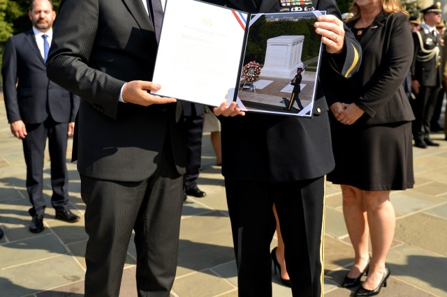Maj. Gen. Bradley A. Becker, commanding general, Joint Force Headquarters-National Capital Region and the U.S. Army Military District of Washington, presents a certificate to Prime Minister of Italy, His Excellency Matteo Renzi, after laying a wreath at the Tomb of the Unknown Solider in Arlington National Cemetery Oct. 19, 2016.