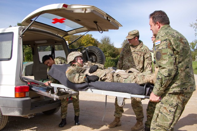 "SLUNJ, Croatia -- Cpt. Charles Blackwell (center), surgeon for 3rd Squadron, 2nd Cavalry Regiment, U.S. Army, supervise medics from Croatian Land Forces place a simulated patient in a Croatian ambulance during Puma 16 Oct 13, 2016 at Military Training Area Eugen Kvaternik. The medics practiced evacuating a simulated casualty in a Stryker Medial Evacuation Vehicle from the point of injury at the farthest location in the training area to the ambulance exchange point. The Iron Troop is training in Croatian with 2nd Mechanized Battalion ""Puma"" of the Guard Armored-Mechanized Brigade, Croatian Land Forces. (Photo by: Staff Sgt. Jennifer Bunn, 2d Cavalry Regiment Public Affairs)"