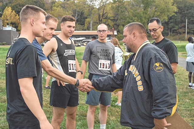 Danny Howell, FMWR sports specialist, congratulates 554th Engr. Bn. team members, from left, Connor Wernecke, Hunter Aquirre, Patrick Richardson, Ryan Doblar and Stephano Porter after presenting them with the 2017 Commander's Cup Cross-Country Road Race championship trophy Friday at Piney Valley Golf Course.
