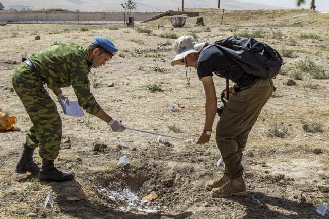 Two students participating in the Humanitarian Mine Action training course measure an Improvised Explosive Device blast hole during a practical exercise Sept. 29, 2016 in Tajikistan. U.S. Army Soldiers, in support of U.S. Army Central, certified 39 participants from Tajikistan, Kazakhstan, Kyrgyzstan, Afghanistan and Armenia on explosive hazard mitigation in accordance with the International Mine Action Standard.