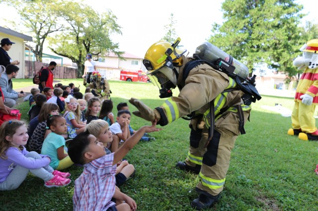 """Camp Zama firefighter gives """"high fives"""" to kids at the SFHA CDC Oct. 12 for Fire Prevention Week held Oct. 8-15. (U.S. Army photo by Lance D. Davis)"""