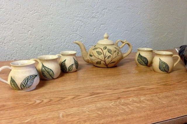"""Spc. Dmitriy Pinchuk, a Russian linguist at Fort Stewart, Ga., won first place in the ceramic art for novices category in the Army Arts and Crafts Contest ran by U.S. Army Installation Management Command's G9 Family and Morale, Welfare and Recreation Directorate. His work """"Tea Leaves"""" include a hand-carved teapot and matching cups."""