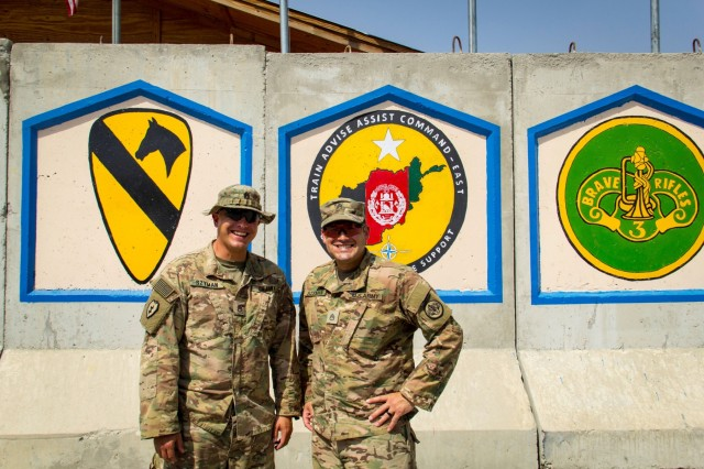 U.S. Army Staff Sgt. Mark Szyman (left), and his brother Staff Sgt. Nicholas Szyman in front of the Train, Advise and Assist Command-East headquarters in eastern Afghanistan Sept. 10, 2016. The brothers are currently deployed together with the 3rd Cavalry Regiment.