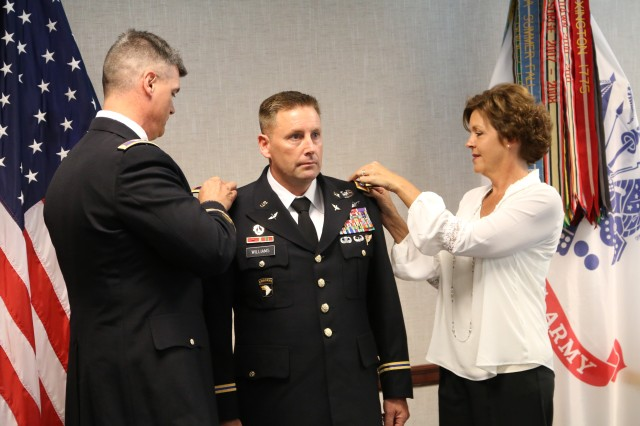 During his Oct. 14 promotion ceremony at the Aviation and Missile Command, Col. Michael Williams dons the shoulder boards by Col. Shawn Prickett and Colonels' wife, Carrie.
