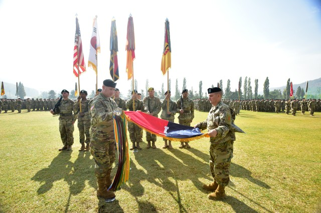 "Col. Timothy Hayden (left), 1st Armored Brigade Combat Team, 1st Infantry Division and Command Sgt. Maj. Dale Sump, 1st ABCT, 1st ID command sergeant major, ""un-case"" the brigade's colors during a Transfer of Authority ceremony held at Camp Casey on October 27. 1st ABCT, 1st ID is assuming the rotational mission conducted by 1st ABCT, 1st Cavalary Division for the last nine-months."
