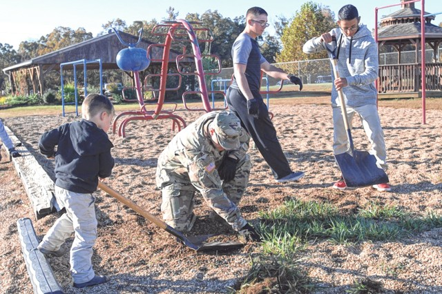 Volunteers, including engineer Soldiers and Family members, clean up the playground at Thayer Elementary during the annual Make a Difference Day Saturday. More than 30 Fort Leonard Wood-connected organizations took part in dozens of volunteer service projects around the installation and in surrounding communities.