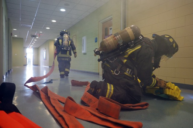 Camp Humphreys firefighters prepare their fire hoses during a structural drill at Humphreys Central Elementary School on Oct.12. The drill was part of Fire Prevention Week activities the fire department put on for the community.