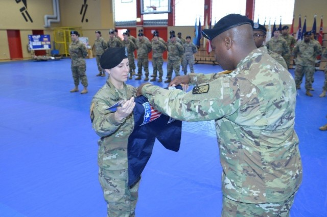 BAUMHOLDER, Germany -- Capt. Katherine Hansen, the inaugural commander of the 569th Human Resources Company, 16th Special Troops Battalion, unfurls the new unit guidon Oct. 25 at the Hall of Champions on Smith Barracks. (Photo by Staff Sgt. Daniel Wyatt, 16th Sustainment Brigade Public Affairs)
