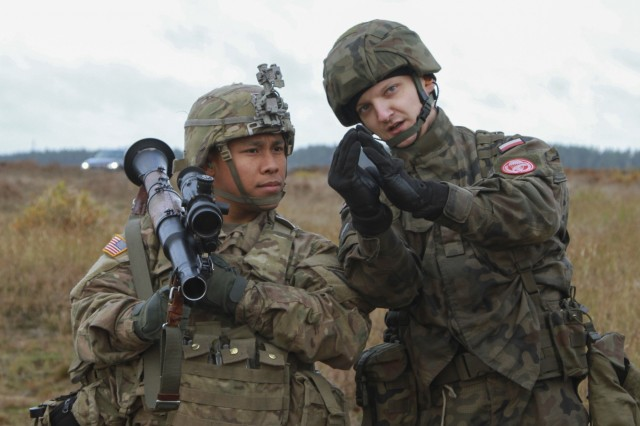 """DRAWSKO POMORSKIE, Poland - Spc. Jacob Quitugua, Paratrooper, Company D, 2nd Battalion, 503rd Infantry Regiment, 173rd Airborne Brigade, holds an RPG-7D Anti-Tank Grenade Launcher while Polish Pvt. Pawe� Tylek, paratrooper, 16th Polish Airborne Battalion, 6th Airborne Brigade, describes the proper sight picture of the weapon during anti-tank training in Studnica, Poland, Oct. 29, 2016. The training provided both U.S. and Polish forces cross training on the M136 AT4 anti-tank weapon and the RPG-7D Anti-Tank Grenade Launcher. The """"Sky Soldiers"""" of D Co., 2nd Bn., 503rd Inf. Regt., are on a training rotation in support of Operation Atlantic Resolve, a U.S. led effort in Eastern Europe that demonstrates U.S. commitment to the collective security of NATO and dedication to enduring peace and stability in the region. The 173rd Airborne Brigade, based in Vicenza, Italy, is the Army Contingency Response Force in Europe, and is capable of projecting forces to conduct a full range of military operations across the United States European, Central and Africa Command areas of responsibility within 18 hours. (U.S. Army photo by Sgt. Lauren Harrah/Released)"""