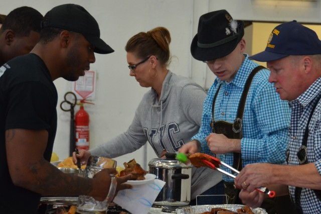 ILLESHEIM, Germany (Nov. 1, 2016) -- Volunteers from the U.S. Army Garrison Ansbach community lade out traditional German fest foods to Soldiers of the 3rd Battalion (Assault Helicopter), 501st Aviation Regiment, Combat Aviation Brigade, 1st Armored Division. With the help of several USAG Ansbach private organizations and local businesses, 3-501st celebrated Oktoberfest Oct. 21 at a hangar here at Storck Barracks, where the battalion is rotationally stationed. (U.S. Army photo by Bryan Gatchell, USAG Ansbach Public Affairs)