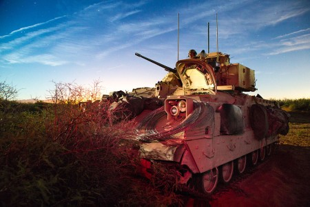 Pvt. Zachery T. Strother, assigned to 1st Platoon, A Company, 40th Engineering Battalion, watches for enemy movement from a staged attack position in an M2 Bradley Fighting Vehicle while conducting training maneuvers during the 2016 Army Warfighting Assessment (AWA) 17-1, at Fort Bliss, Texas, Oct. 17, 2016. The AWA was conducted to assess operational effectiveness.