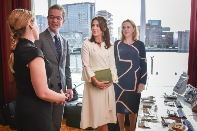 """Eryn Flynn (far left), an education and outreach coordinator at the Natick Soldier Research, Development and Engineering Center's Combat Feeding Directorate, presents a table-top display of combat rations to (from left to right) the Minister for Environment and Food, Esben Lunde Larsen (second from left), Crown Princess Mary of Denmark (center), and Karen Haekkerup, CEO, Danish Agriculture & Food Council (far right), during the Danish hosted """"Drivers of Food Innovation in the U.S. and Denmark"""" seminar held at the Intercontinental Hotel in Boston, Massachusetts, Sept. 30."""