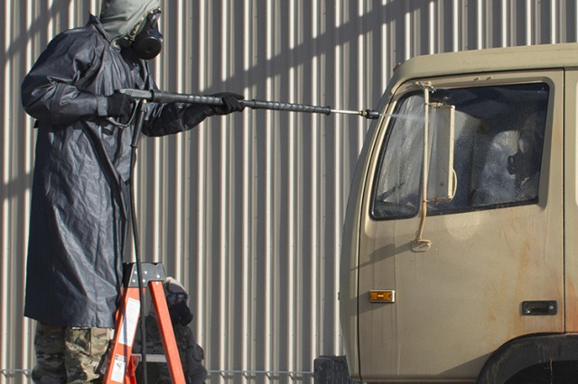 A Soldier demonstrates how a truck is decontaminated after a chemical or biological attack or incident, during an Oct. 20, 2016 demonstration of emerging decontamination technologies at Dugway Proving Ground, Utah. The demonstration was hosted by Department of Defense's Joint Program Manager for Protection office. In accordance with international treaties, only simulated agent is used outdoors. Photo by Al Vogel, Dugway Public Affairs
