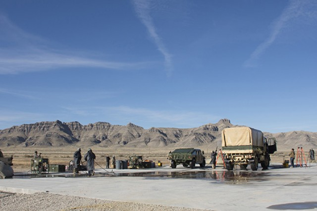 Soldiers demonstrate the decontamination of a truck on a large concrete pad created at Dugway Proving Ground, Utah for the Oct. 20, 2016 CONMIT (Contamination Mitigation) & Technical Demonstration. The helicopter contains the CBRN Aircraft Survivability Barrier, to remove personnel without spreading contamination to helicopter or crew. Photo by Al Vogel, Dugway Public Affairs
