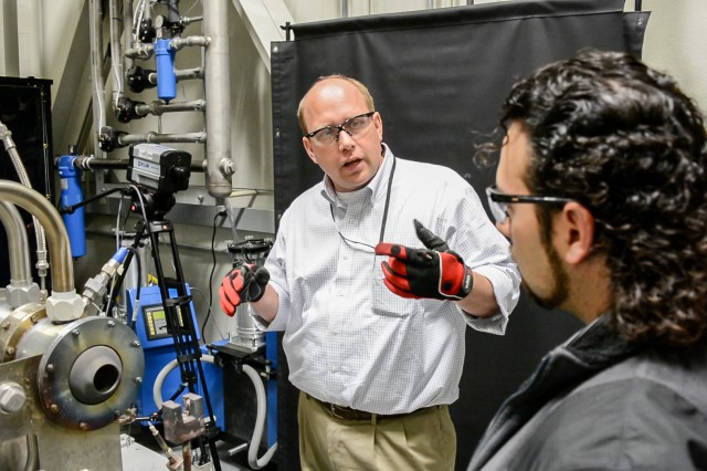Army scientist Dr. Michael Walock (left) explains the operation of the U.S. Army Research Laboratory's hot particulate ingestion rig to ARL post-doctoral fellow Dr. Andy Nieto.