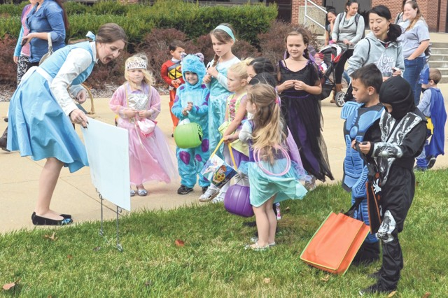 Costumed children listen to a page being read during the Bruce C. Clarke Library's Halloween StoryWalk Oct. 26 at the MSCoE Plaza. Dozens of children and their parents participated in the annual event designed to encourage reading.