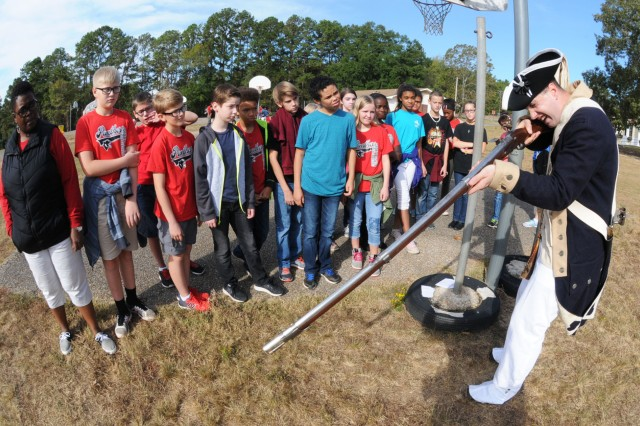 Spc. Jonathan Addis, HHC, 1-212th Avn. Regt., shows students at Fort Rucker Elementary School how to properly load and fire a musket similar to those using during the Revolutionary War.