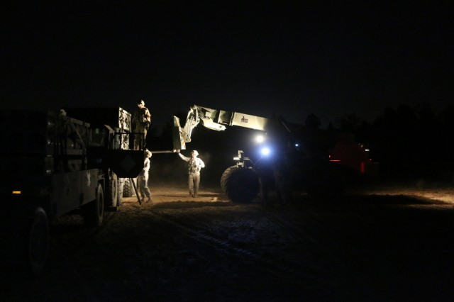 FORT BRAGG, N.C. --Soldiers from the 188th Brigade Support Battation load HIMARS rocket artillery pods during night operations at the Operation Steel Arakh field training exercise, Oct. 29. ( U.S. Army Photo by Capt. Devon Thomas, 18th Field Artillery Brigade Public Affairs/Released)
