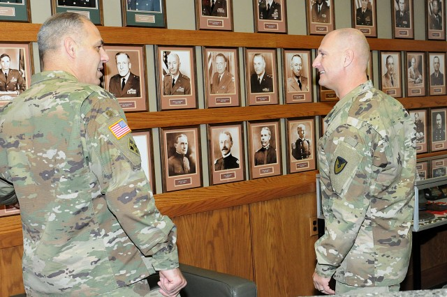 Gen. Gustave Perna (left), commanding general, Army Materiel Command, and Maj. Gen. Edward Daly, commanding general, U.S. Army Sustainment Command, admire the photographs of past Rock Island Arsenal senior commanders before attending an operational briefing at ASC headquarters, Rock Island Arsenal, Illinois, Oct. 26.