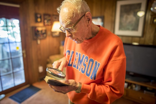 Former U.S. Army 1st Lt. William H. Funchess, 89, reads from a Bible he kept throughout his 34 months as a prisoner of war during the Korean War, Sept. 21, 2016. Funchess was held in the same prison compound as Army Chaplain Father Emil J. Kapaun, who received the Medal of Honor posthumously in 2013 for his acts of courage and compassion as a prisoner of war and is under consideration for Sainthood by the Vatican. Funchess and Kapaun read from this Bible together on many occasions before Kapaun succumbed to starvation and disease. (U.S. Army photo by Staff Sgt. Ken Scar)
