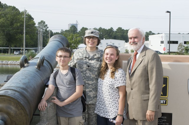 Nancy Waldron stands with her two children and Joe Fitzgerald, North Alabama's civilian aide to the secretary of the Army, next to 18th century cannons that were placed at the U.S. Army Security Assistance Command's headquarters as part of the command's 50th anniversary celebration at Redstone Arsenal, July 21, 2015.