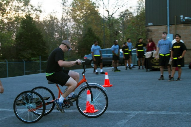 """A Soldier from 101st Special Troops Battalion, 101st Airborne Division (Air Assault) Sustainment Brigade, 101st Abn. Div., maneuvers a bicycle around cones, Nov. 3, 2016, next to the brigade's resiliency center building while wearing goggles that simulate a high alcohol consumption level. Fort Campbell's Army Substance Abuse Program ran the event as part of the brigade's """"Not in My Squad"""" Week. (U.S. Army photo by Sgt. Neysa Canfield/101st Airborne Division Sustainment Brigade Public Affairs)"""