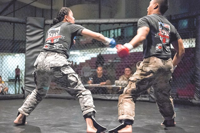 Pfc. Cindy Perez, 5th Engineer Battalion, takes a swing at Spc. John Suarez, 5th Engr. Bn., during their Lightweight match Friday.