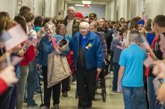Veterans and their families walk down the halls the Rockridge Junior High during the school's Veterans Day event in Taylor Ridge, Illinois, Nov. 10. (Photo by Kevin Fleming, ASC Public Affairs)