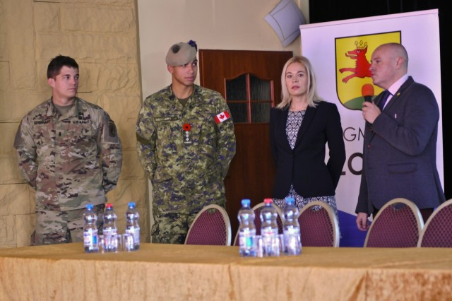 (left to right) U.S. Army 1st Lt. Logan Gearhart, platoon leader, Company D, 2nd Battalion, 503rd Infantry Regiment, 173rd Airborne Brigade, stands with Capt. Ward Lentz, 1st Battalion, Princess Patricia Canadian Light Infantry, as they listen to the City of Lobez' mayor, Piotr Cwikla, during his speech at an operations presentation and static display at the Lobez Culture Center in Poland, Nov. 10, 2016. The attendees were taught how the U.S., Canada and Poland share Nov. 11 as a national holiday and were familiarized with the Troops' equipment. (U.S. Army photo by Sgt. William A. Tanner)