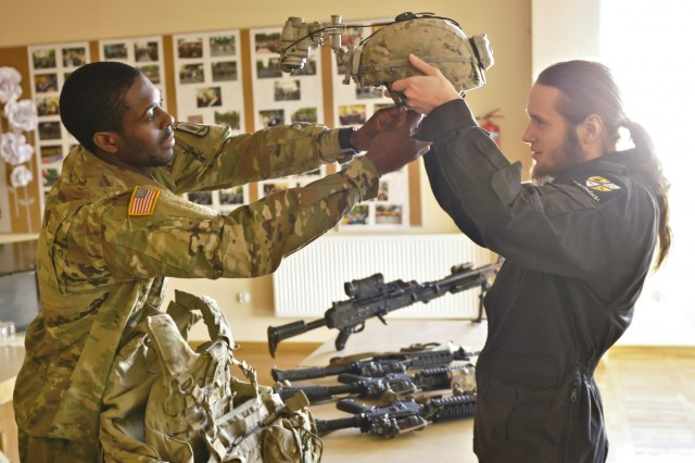U.S. Army Spc. Desmond Lee, infantryman, Company D, 2nd Battalion, 503rd Infantry Regiment, 173rd Airborne Brigade, shows a high school student how to put on a combat helmet during an operations presentation and static display at the Lobez Culture Center in Poland, Nov. 10, 2016. The attendees were taught how the U.S., Canada and Poland share Nov. 11 as a national holiday and were familiarized with the Troops' equipment. (U.S. Army photo by Sgt. William A. Tanner)
