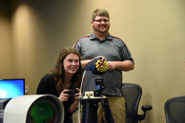 Keri Phillips, a junior at Whitesburg Christian Academy, shoots a weapon system simulation in the U.S. Army Space and Missile Defense Command/Army Forces Strategic Command's Concepts Analysis Laboratory during the 2016 Adventures in Engineering Day Nov. 9 while Brett Hokr, SMDC SMART intern, looks on. High school juniors from throughout the Tennessee Valley toured SMDC, the U. S. Army Aviation and Missile Research Development and Engineering Center, or AMRDEC, Software Engineering Directorate, AMRDEC Prototype Integration Facility, Missile and Space Intelligence Center and the NASA Marshall Space Flight Center.