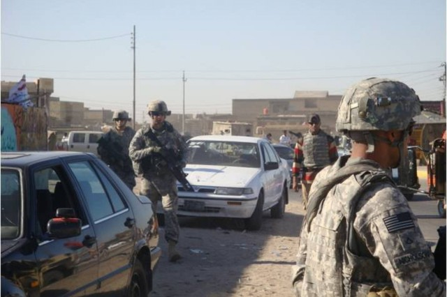 Soldiers from Alpha Company, 1st Battalion, 12th Cavalry Regiment, 3rd Advise and Assist Brigade, 1st Cavalry Division work their way through busy streets to ensure security stability in Basra province near Contingency Operating Base Basra, Iraq, Oct. 1, 2011.