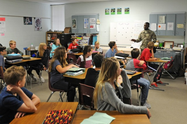 Spc. Adonis Blackwood, Regimental Engineer Squadron, 3d Cavalry Regiment, joins a 7th grade social studies class Nov. 11 at Leander Middle School to answer questions students have about the Army. The visit was part of the schools Veteran's Day celebration. (US Army photo by Spc. Erik Warren, 3d Cavalry Regiment Public Affairs) (Released)