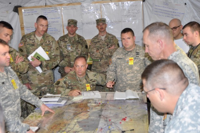 New York Army National Guard aviation Soldiers assigned to the 42nd Combat Aviation Brigade ponder their next move over a map of the area of operations in their command post during a two-week Warfighter command post exercise at Fort Indiantown Gap on Thursday, Nov. 10, 2016. The exercise is testing the staff skills the Soldiers need to handle a variety of complex aviation missions.