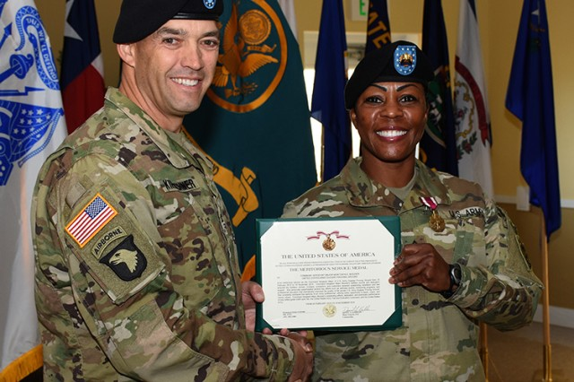 Col. Sean Kirschner, commander of Dugway Proving Ground, gives Command Sgt. Maj. Montonya Boozier the Meritorious Service Medal before the Nov. 15, 2016 Change of Responsibility ceremony that replaced her with Command Sgt. Maj. Joe A. Bonds. Boozier will be assigned to U.S. Army Central Command at Shaw Air Force Base, South Carolina. Photo by Al Vogel, Dugway Public Affairs