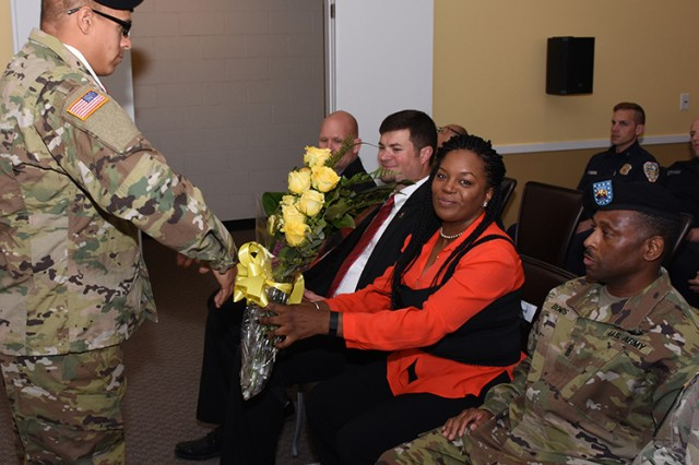 Rhonda Ewell receives a dozen yellow roses as thanks for supporting Command Sgt. Maj. Joe A. Bonds as a friend, during Bonds' Nov. 15, 2016 installation as the new command sergeant major at Dugway Proving Ground, Utah. Bonds and Ewell have been friends since high school. Photo by Al Vogel / Dugway Public Affairs