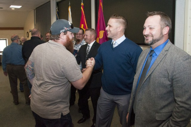 Attendees at the of the Rock Island Arsenal-Joint Manufacturing and Technology Center's Machinist Apprentice Program commencement ceremony congratulate graduates following the event in the Baylor Conference Room, Building 103, RIA, Illinois, Nov. 4.
