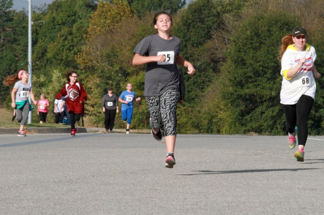 Bailey Marshall (center) sprints the final 100 yards past Sarah DeSadier (right) to the finish line during the Veterans 5K Fun Run/Walk at McAlester Army Ammunition Plant, Oklahoma, November 5. Marshall finished third in the girl's 13 years and under category in 51 minutes and 38.72 seconds.