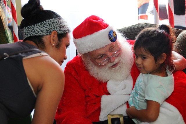 Arianna Ruano, military family member, sits in Santa's lap, as her mother, Patrisha, gets ready to take a photo during the HollyDay Bazaar at Yano Hall Nov. 12.