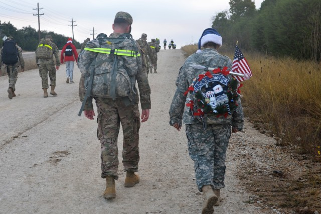 Two Soldiers from Headquarters Company, 13th Expeditionary Sustainment Command trudge up the final hill during a ruck march to donate toys to Santa's Workshop on Nov. 17, 2016.