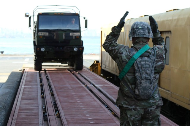 A Soldier from 2ID SBDE signals the convoy driver with his hands to stage an LMTV safely on the rail in coordination with 19th ESC's 517th MCT. (Photo by Pfc. Sin, Jae-hyung).