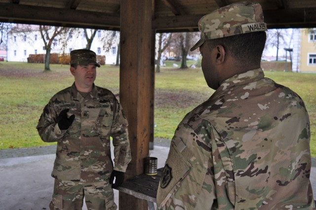 "VILSECK, Germany -- Sgt. Robert Yarbrough (left) and Staff Sgt. James Walker, both smokers,  discuss a BMEDDAC smoking cessation card during a work break under a pavilion on Rose Barracks during the Great American Smokeout, 17 Nov.  Both Soldiers elected to use the Smokeout day to quit ""cold turkey"" but Yarbrough carried a few extra cards to hand out to fellow Soldiers who had mentioned they were thinking about participating in the Smokeout or eventually quitting.  U.S. Army Medical Department Activity Bavaria (BMEDDAC) clinic staffs in Ansbach, Grafenwoehr, Hohenfels, Stuttgart and Vilseck reached out to members of their respective communities 17 November at post exchanges, MWR venues and dining facilities in order to inform and encourage both tobacco smokers and dippers to quit for 24 hours. This year clinic representatives handed out special cards, ""Time to Quit Tobacco?"" with contact info to all clinics and make it easy for anyone considering quitting tobacco -- or anyone who knows and wants to encourage a smoker or dipper to quit.   To learn more about the people and facilities of the U.S. Army Medical Department Activity Bavaria (BMEDDAC) and the clinics they support in Ansbach, Grafenwoehr, Hohenfels, Stuttgart and Vilseck visit the BMEDDAC website at http://rhce.amedd.army.mil/bavaria"
