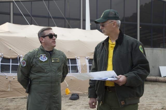 Colombian Air Force Col. Juan C. Rocha, 12th Air Force, Air Forces South liaison officer, talks with Michael Bozzo of the South Carolina Forestry Commission's Incident Management Team during a State Partnership Program Engagement to the Incident Command Center as South Carolina Army National Guard CH-47 Chinook and UH-60 Black Hawk crews work to support the South Carolina Forestry Commission to contain a fire near the top of Pinnacle Mountain in Pickens County, South Carolina, Nov. 15, 2016.  The aircraft are equipped with a Bambi Buckets, which can be filled with any available water to be transported and dumped on the fire.
