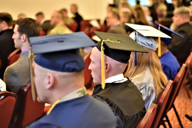 Graduates representing different colleges and universities sit together during U.S. Army Garrison Ansbach's Graduate Recognition Ceremony Nov. 16, 2016, at the Von Steuben Community Center in Ansbach, Germany. The ceremony highlighted the achievements of 35 college graduates from among 18 institutions of higher learning.