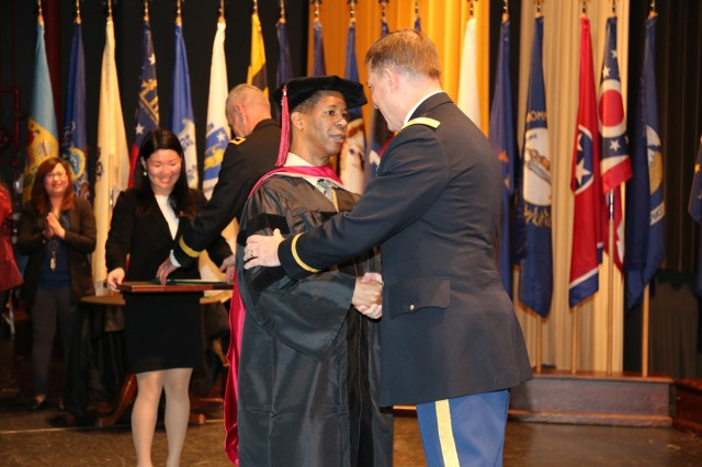 Col. William B. Johnson, commander of U.S. Army Garrison Japan, congratulates Irvin Taylor, acting deputy to the Garrison Commander for US Army Garrison Japan, who graduates with a doctorate degree during a graduation recognition ceremony hosted by CZEC Nov. 15 at CRC on Camp Zama. (U.S. Army Photos by Noriko Kudo)