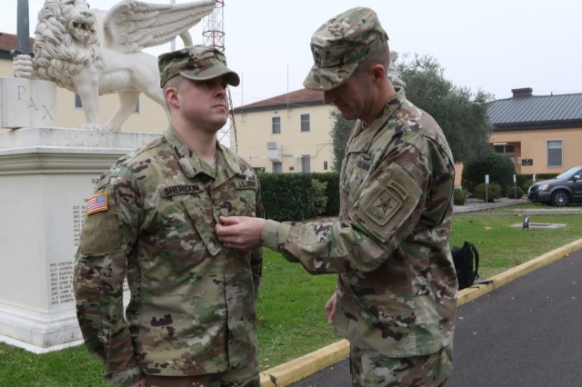 U.S. Army's most senior enlisted leader, Sgt. Maj. of the Army Daniel Dailey, promotes a junior enlisted Soldier, Spec. James Sheridan, one of U.S. Army Africa's command drivers, to the rank of Sergeant, Nov. 17, 2016, in front of the USARAF headquarters on Caserma Ederle in Vicenza, Italy. The promotion to sergeant marks a pivotal role change in a Solider's career from one who is given tasks to one who gives tasks. On this day, Sheridon also celebrates his tenth year of military service, which includes 3-years as active duty and a combined 7-years with Michigan's Army and Air National Guard. (U.S. Army Africa photo by: Staff Sgt. Lance Pounds)