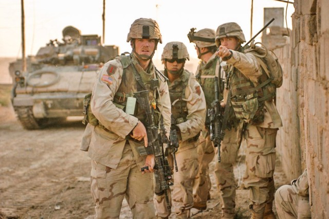 Captain Dean W. Morisson, Executive Officer with the 1st Infantry Divisions 3rd Brigade Reconnaissance Troop, directs Staff Sgt. Nicholus Danielsen, acting platoon sergeant with the troop, while conducting clearing operations in Fallujah Nov. 15, 2004, during Operation Al-Fajr.