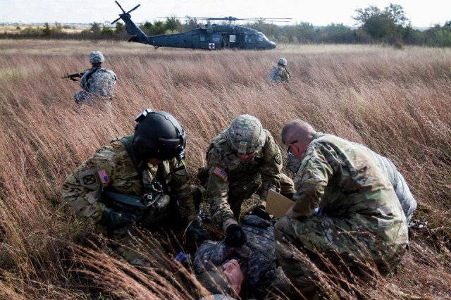 """A flight medic with the 1st Air Cavalry Brigade """"Warriors"""" (left) assists Soldiers with the 303rd MI Battalion in preparing a simulated casualty for medical evacuation during training, while a trainer/evaluator from the 1st Medical Brigade (far right) looks on, Nov. 17."""