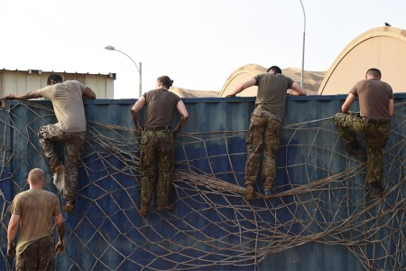 Service members from Combined Joint Task Force-Horn of Africa Civil Affairs climb over an obstacle during a mud run hosted by the French military, Nov. 6, 2016, in Djibouti, Africa. The event allowed coalition forces from French, Japanese, and American teams to interact and build camaraderie while navigating a five kilometer course. The French 5th Marine Regiment team took first place.